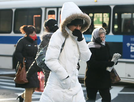A pedestrian shields herself from the cold in Illinois. (erockford.com)
