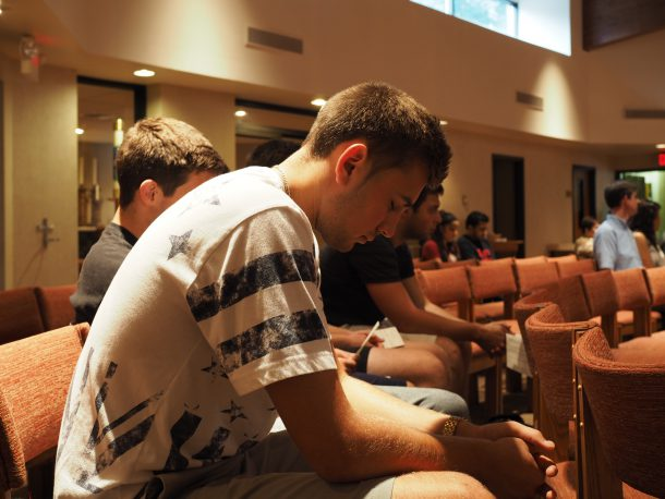 Kruschef Sanchez // The Crown First-year business management student Joe Leonardi joins in prayer during the Interfaith Prayer Service.