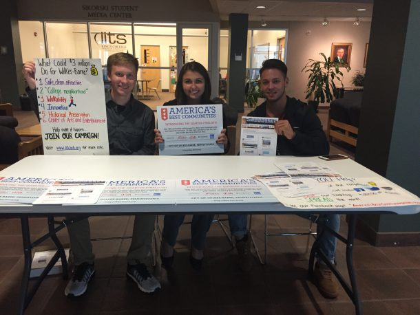 Catherine Aiello//The Crown From left to right: Liam Holden, Arielle Belskis and Brandon Espinoza, students from Penn State Wilkes-Barre, sit in the Campus Center at King's College to spread word of Wilkes-Barre's nomination in America's Best Communities competition.